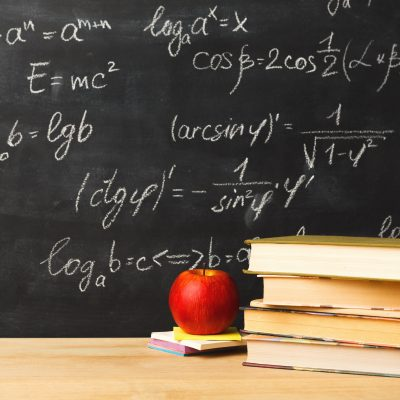 Studying mathematics educational background. Books pile and apple against classroom blackboard with chalk writing of sums. Back to school, research concept