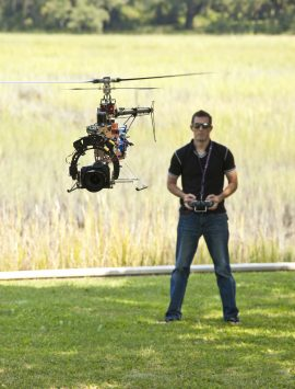 Man controlling helicopter drone, UAV with SLR camera attached.